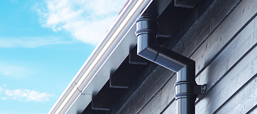 Black aluminium traditional round downpipe and white moulded ogee guttering