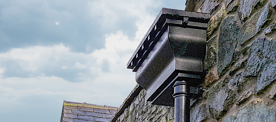Black ornate aluminium hopper head mounted to stone wall
