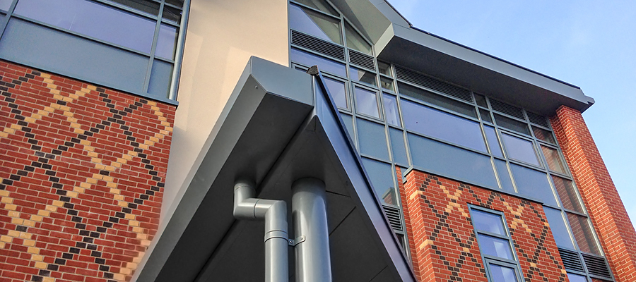 Grey aluminium shaped box gutter fitted to modern build with round downpipes