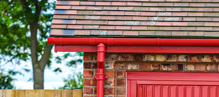 Aluminium red half round guttering with traditional cast round downpipes fitted to outbuilding at Garston Barns